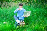 Stock Photo of young man outdoors with a cup and laptop