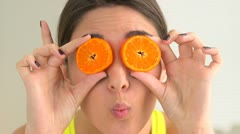 Happy smiling woman making sillyfaces with fruit over eyes Stock Footage