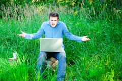 young man outdoors with a cup and laptop - stock photo