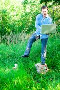 Acrobatic young man outdoors with a cup and laptop Stock Photos