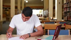 Multi-ethnic university student working in the library - stock footage