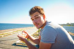young man eating on the beach - stock photo