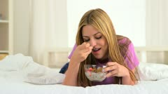 Mexican woman eating cereal in bed - stock footage