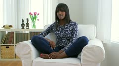 Happy African American woman sitting cross legged on couch - stock footage