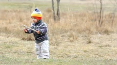 Funny little baby playing with a stick outdoor, throwing off, bending  Stock Footage