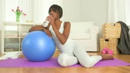 Stock Video Footage of Black woman drinking bottled water after working out