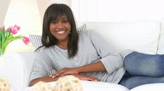 Happy black woman lounging on couch Stock Footage