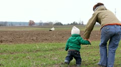 Baby holding mother hand walking together to stork/ hand in hand baby and mother Stock Footage