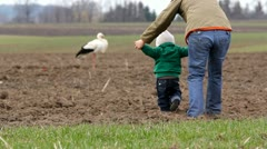 Mother sustaining her baby from his hands walking toward stork Stock Footage