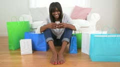 Black woman with shopping bags texting on cell phone - stock footage