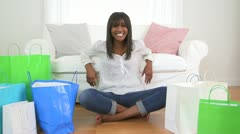 African American woman looking through shopping bags at home - stock footage