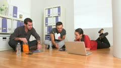 Group of co workers eating food on floor of office Stock Footage