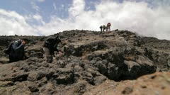 Trekkers stepping on to a rocky outcrop - stock footage