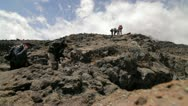 Trekkers stepping on to a rocky outcrop Stock Footage