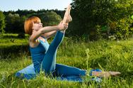 Red woman practicing fitness yoga outdoors Stock Photos
