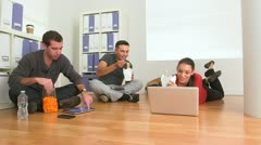 Mexican and Caucasian employees eating food on floor of office Stock Footage
