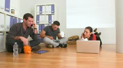 Multi ethnic group of office workers eating food on floor Stock Footage
