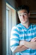 young man at the window - stock photo