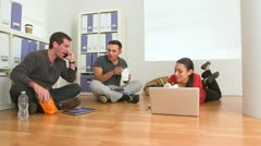 Hispanic and Caucasian office workers eating food on floor Stock Footage