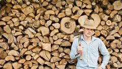 woodcutter with straw hat on a background of wood - stock photo