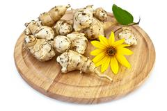 Jerusalem artichoke with a yellow flower on a round board Stock Photos