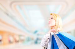 Blonde young woman holding shopping bags looking upwards at copyspace Stock Photos