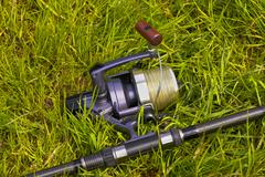 fishing reel on the grass - stock photo