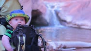 Baby in hiking backpack near waterfall in National Park. Stock Footage