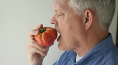Senior eats tomato Stock Footage