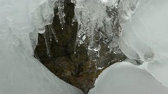 Ice icicles flow melt water drop stones mountain cave Stock Footage