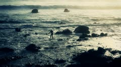 Surfer Heads out to Waves at Sunset Stock Footage