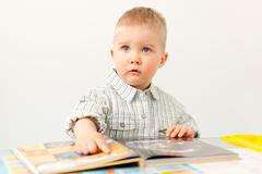 curious baby boy studying with the book - stock photo