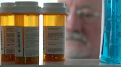 Man takes pill bottle from medicine cabinet and reads label - stock footage