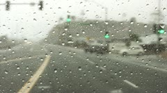 Raindrops on windshield while driving down highway Stock Footage