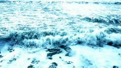 Waves crashing at beach with foam Stock Footage