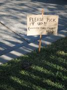 Sign on lawn next to dog waste Stock Photos