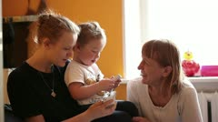 Two year-old boy plays with his mother and grandmother. - stock footage