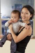 Smiling Korean mother holding baby - stock photo