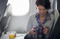 Hispanic woman using camera in airplane - stock photo
