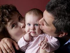 Parents kissing baby's cheeks Stock Photos