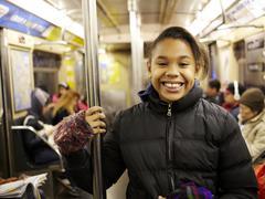 Sekarotuinen tyttö hymyilee metrossa Kuvituskuvat