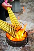 Prayers lighting incense sticks Stock Photos