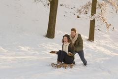 Caucasian man pushing girlfriend on sled in snow Stock Photos
