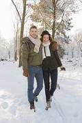 Caucasian couple pulling sled in snow Stock Photos