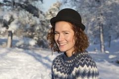 Caucasian woman smiling in snow Stock Photos