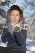 Caucasian woman playing in snow - stock photo