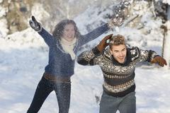 Caucasian couple playing in snow Stock Photos