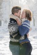 Caucasian couple hugging in snow Stock Photos