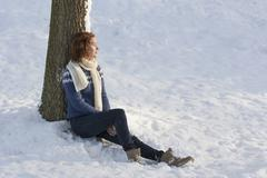 Caucasian woman sitting in snow - stock photo