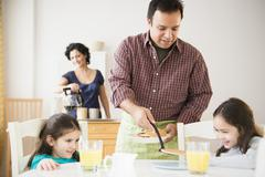 Father serving daughters breakfast at table Stock Photos